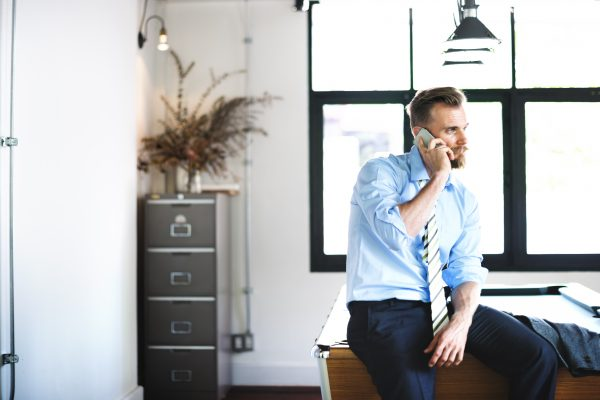 A businessman on the phone to a supplier who has overpaid an invoice in Xero